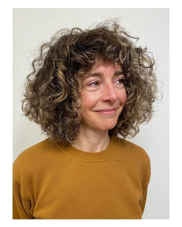 Une frange flatteuse pour les femmes plus âgées aux cheveux bouclés.