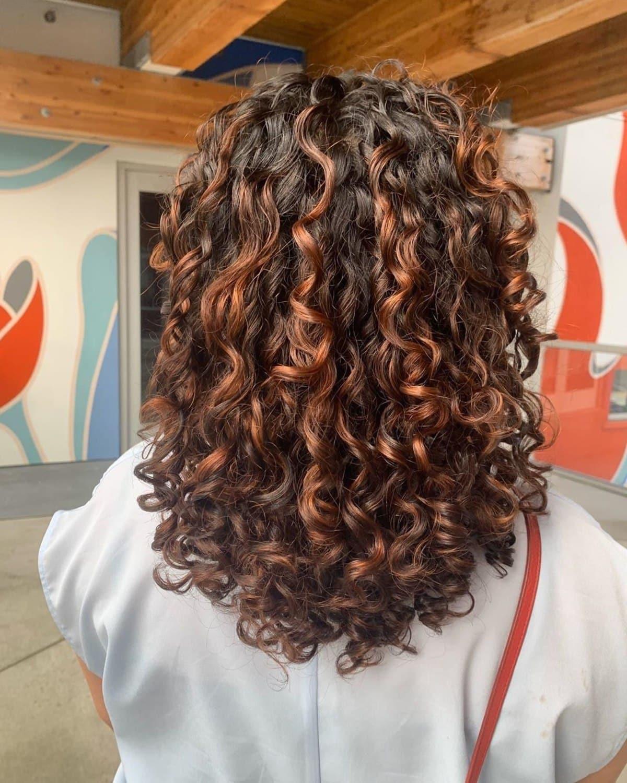 Cheveux frisés roux brunâtres avec mèches