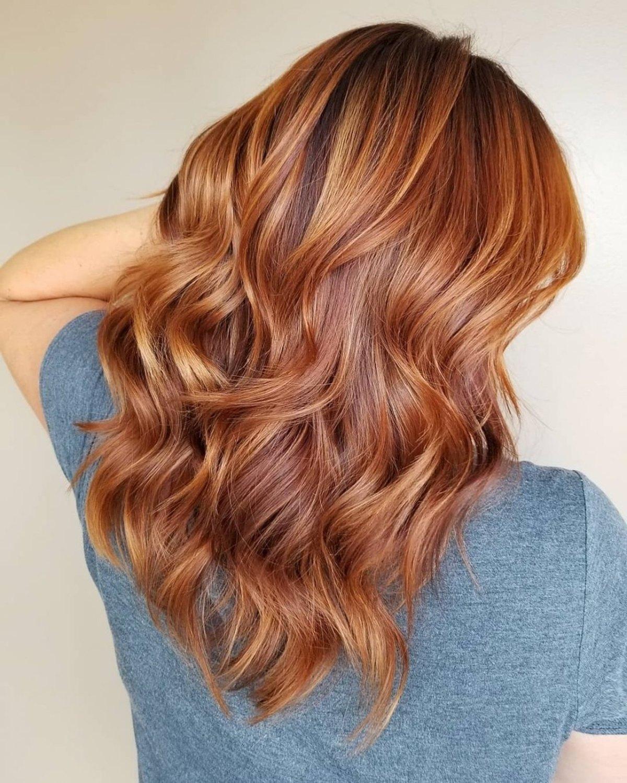 Couleur de cheveux rouge cuivré avec des mèches en or rose.