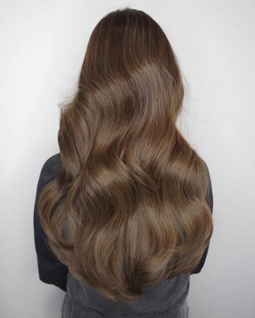Cheveux bruns longs et ondulés avec du volume