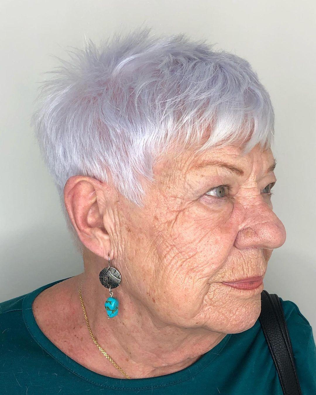 Femme de plus de 70 ans avec des cheveux gris courts et coupés.