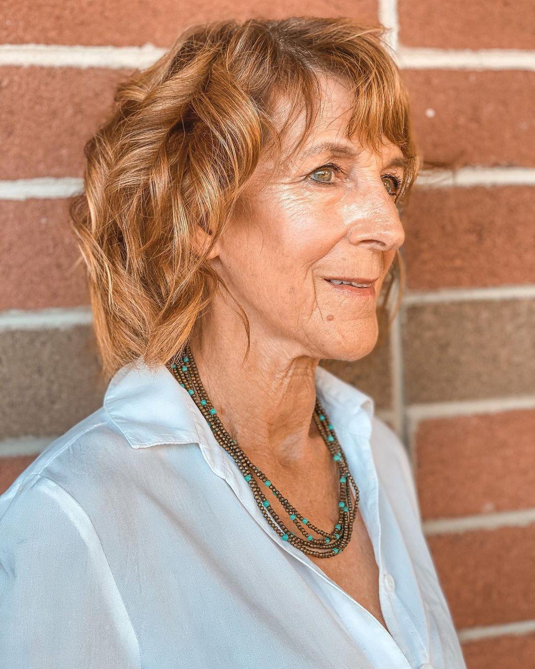 Femme de 70 ans avec une coupe de cheveux ondulée.