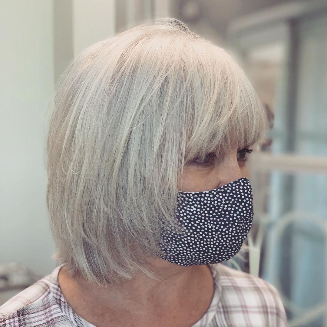 Coupe de cheveux grise dégradée pour les femmes de plus de 55 ans aux cheveux fins.