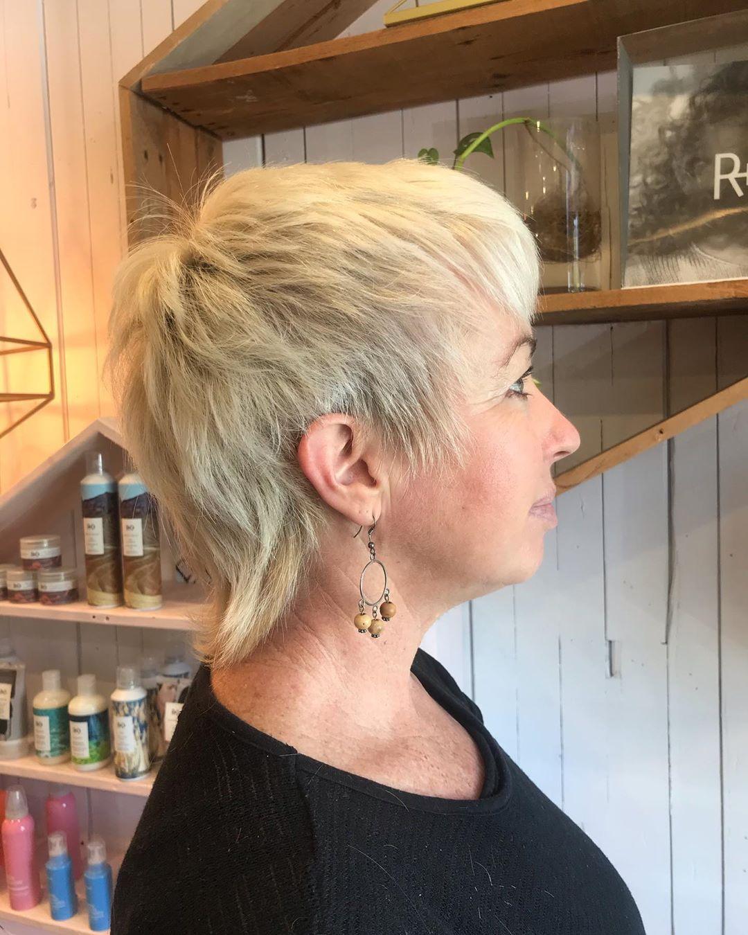 Une femme d'une cinquantaine d'années aux cheveux fins avec une coupe de cheveux shag très courte.