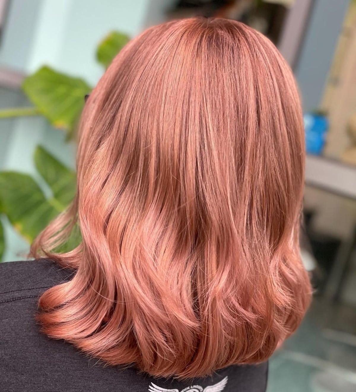 Cheveux blonds mi-longs avec des nuances d'or rose.