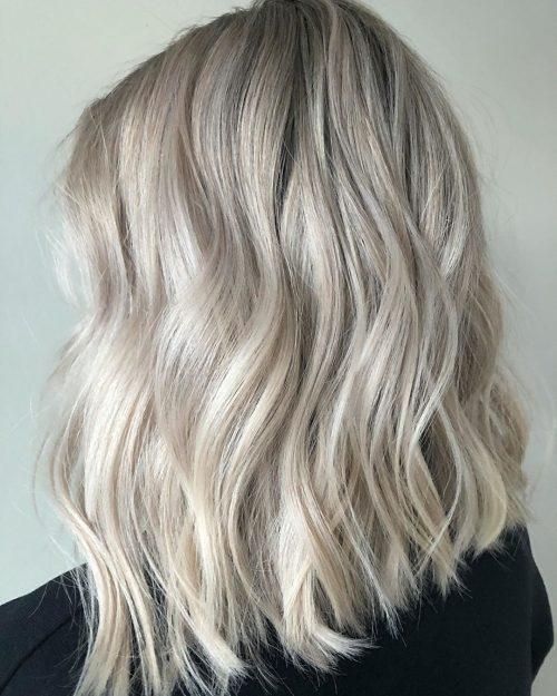 Cheveux mi-longs blonds glacés avec un style Beach Wavy.
