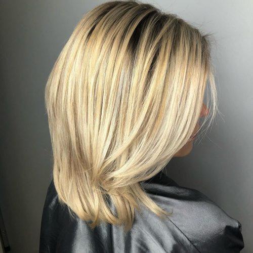 Coupe dégradée mi-longue avec une teinte blond clair