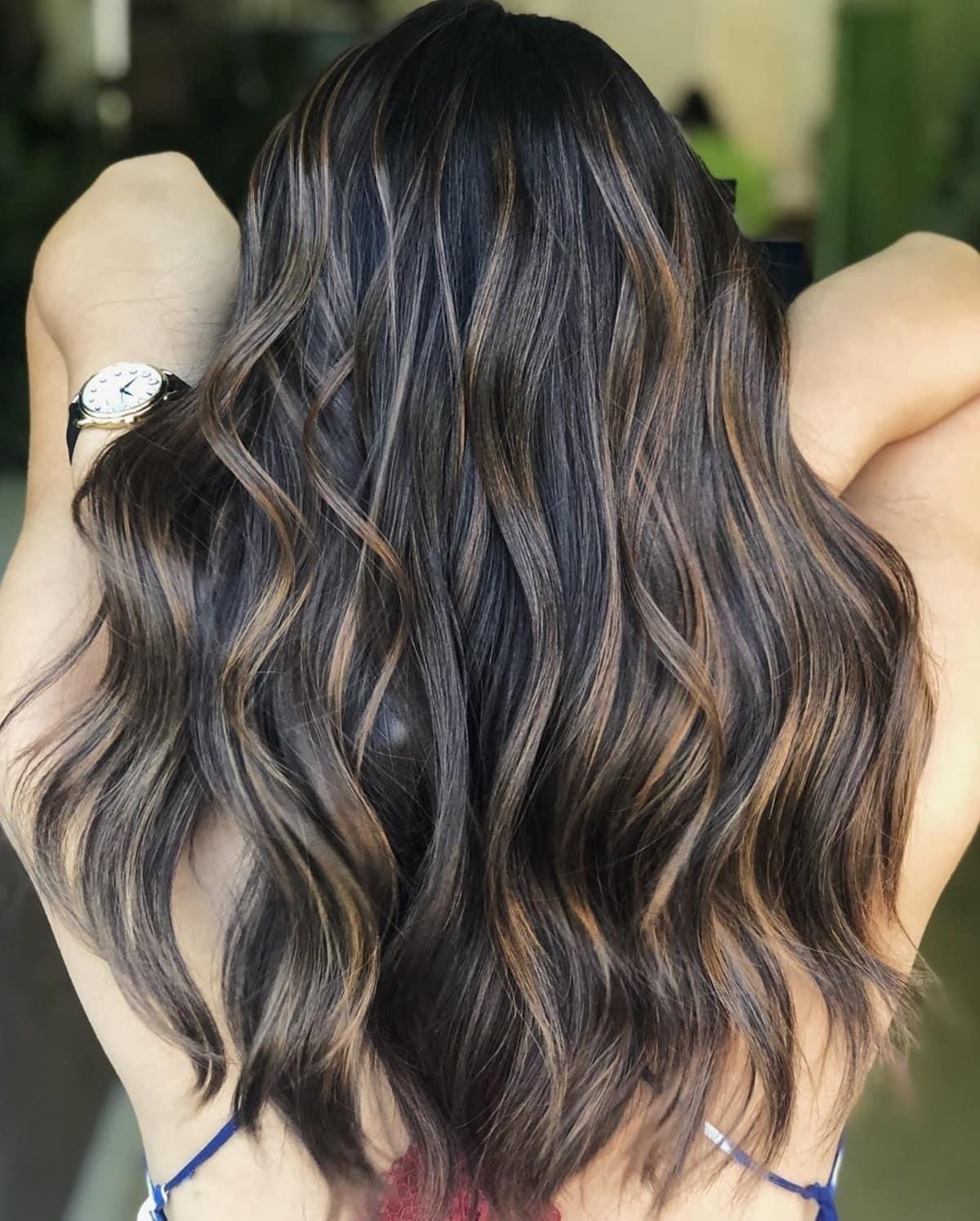 mèches brun auburn sur cheveux noirs ondulés