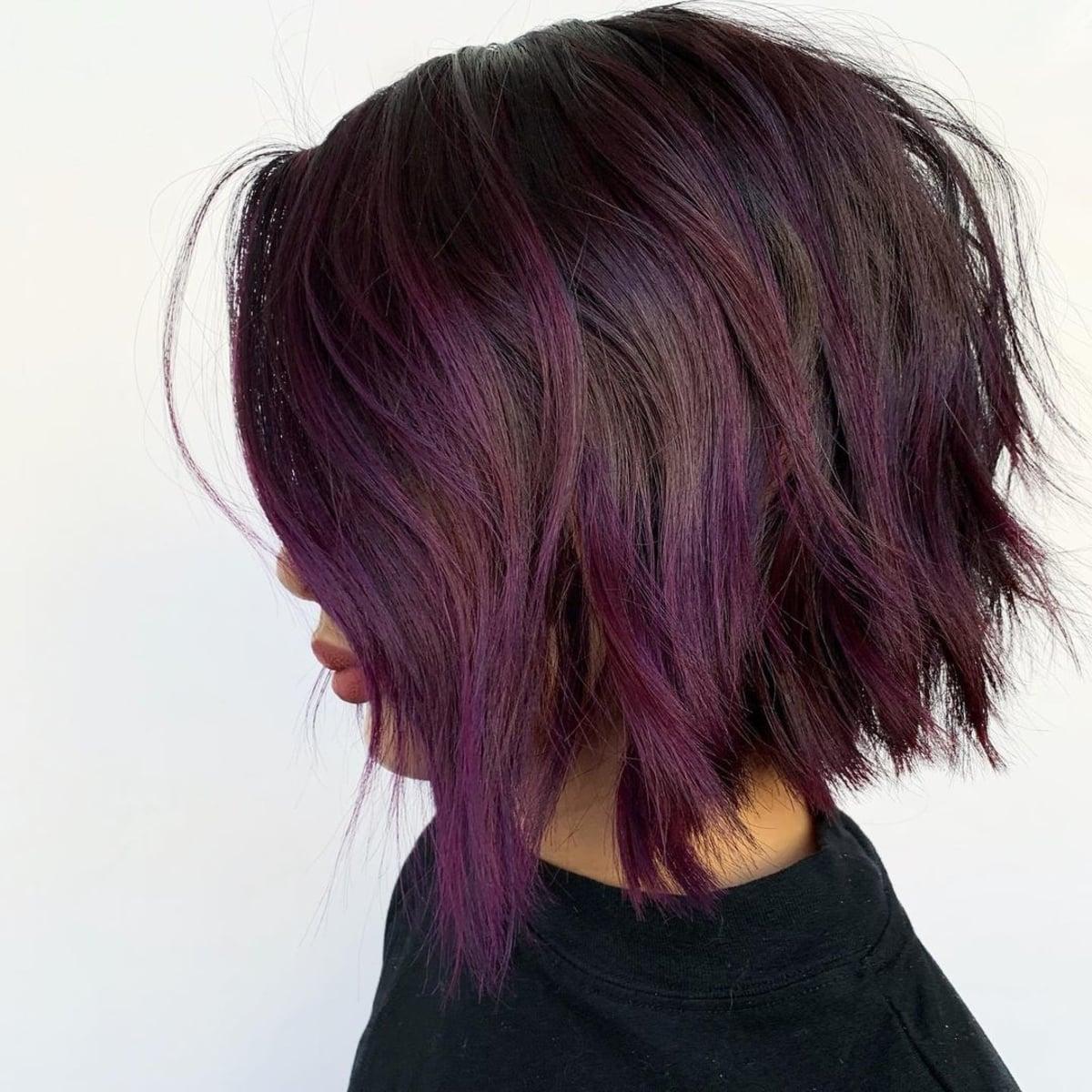 Des tons violets sur des cheveux empilés