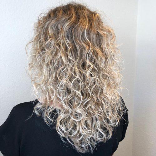Blond foncé à blond clair sur cheveux longs et bouclés