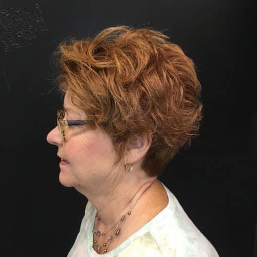 Cheveux courts et bouclés pour les femmes de plus de cinquante ans avec des lunettes.