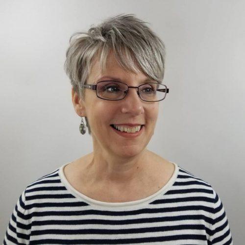 Coupe Pixie avec frange sur une femme de 50 ans avec des lunettes.