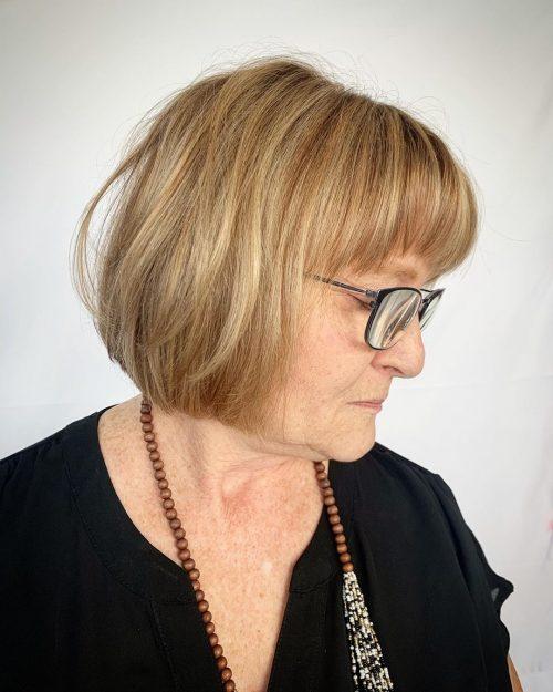 Coiffure Bob longue pour les femmes âgées de plus de cinquante ans avec des lunettes et un visage rond.