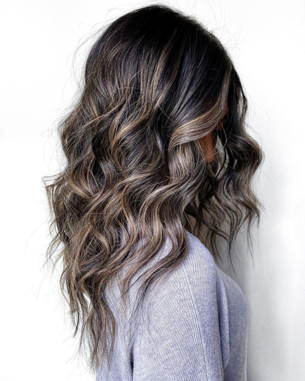 Cheveux foncés avec des mèches blondes et un balayage caramel.
