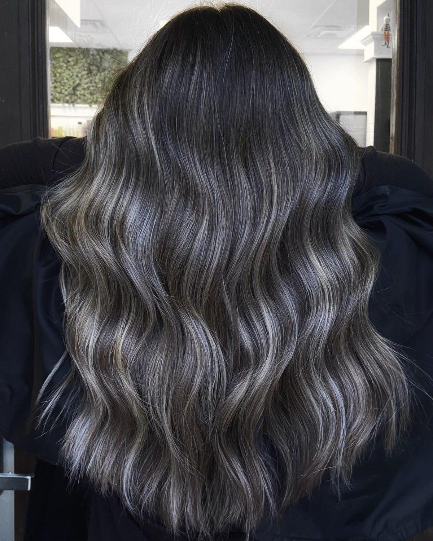 Mèches blondes cendrées sur des cheveux longs foncés