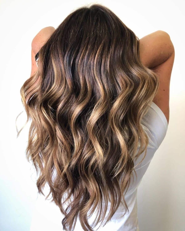 Cheveux bruns foncés avec des mèches ensoleillées.