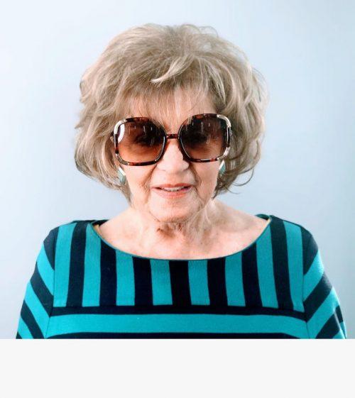 Coupe dégradée pour une personne de 60 ans avec des cheveux gris naturels.