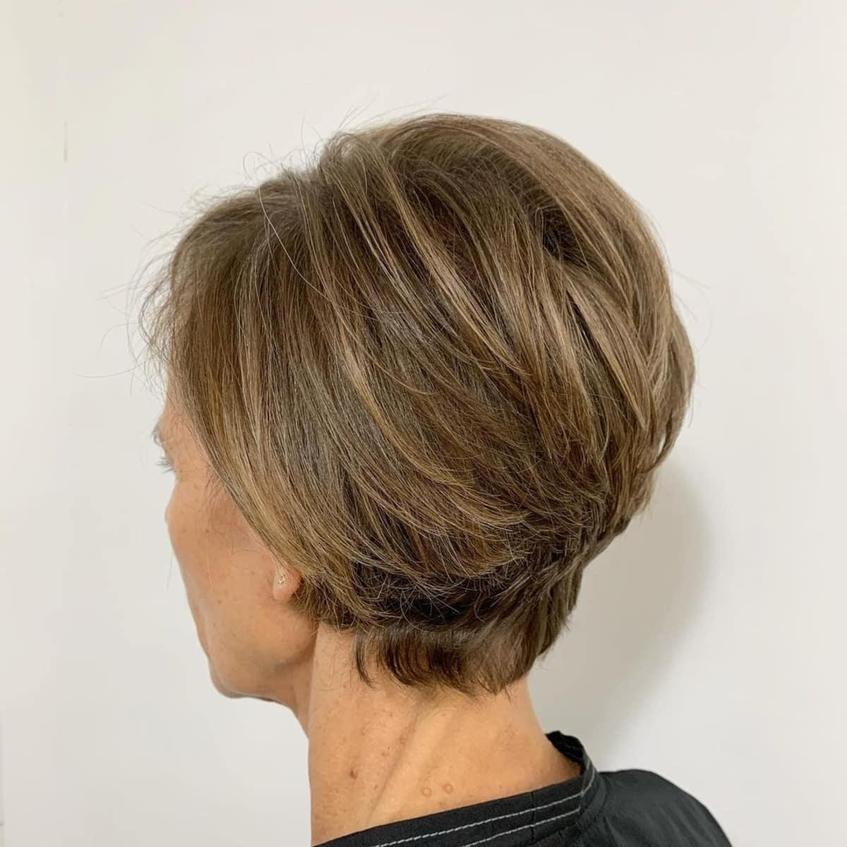 Pixie brun clair avec des mèches subtiles pour les femmes plus âgées.