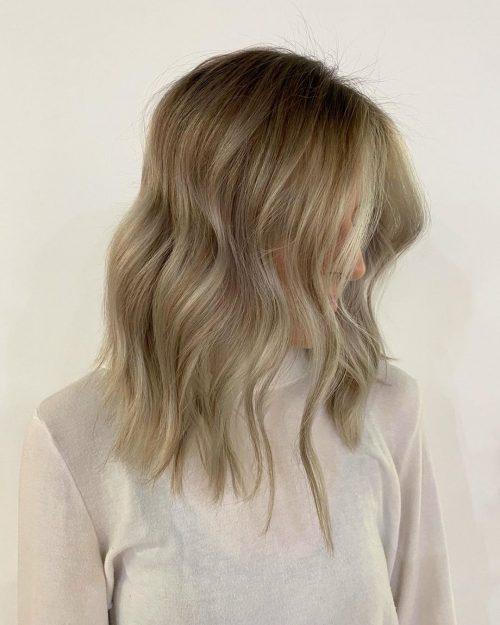 Couleur de cheveux marron clair avec des mèches balayage blondes encadrant le visage.