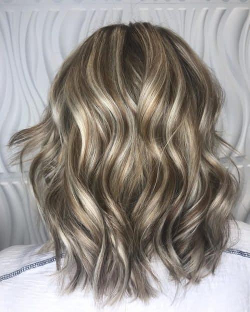 Mèches blondes brillantes sur cheveux bruns foncés