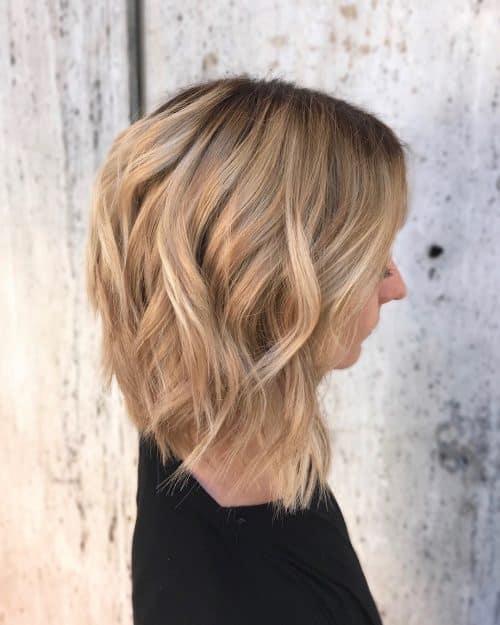 Mèches caramel et blondes sur des cheveux bruns plus clairs avec des racines foncées.