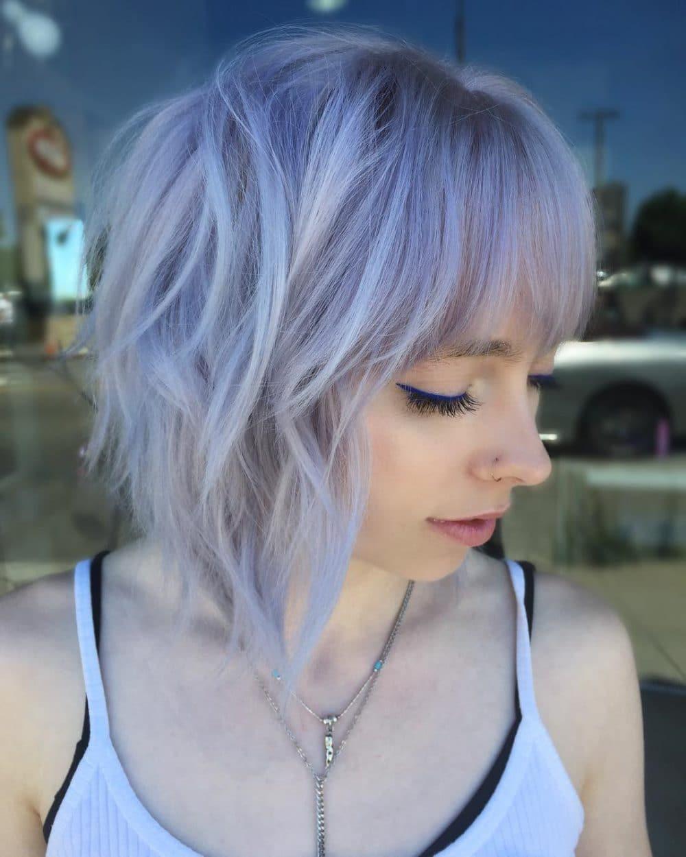 Une coupe courte ébouriffée de cheveux violets.