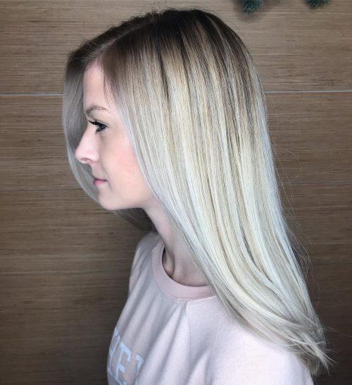 Cheveux blond platine avec des racines naturellement foncées