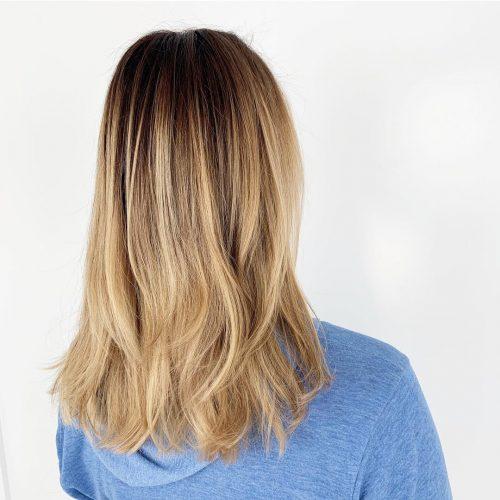 Cheveux blond miel avec des racines brun foncé
