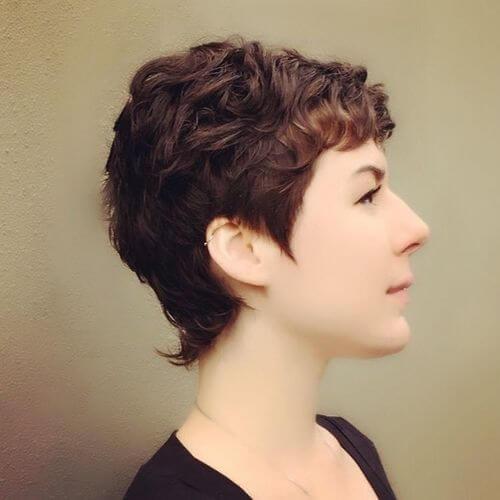 Coupe pixie brune pour cheveux naturellement bouclés.