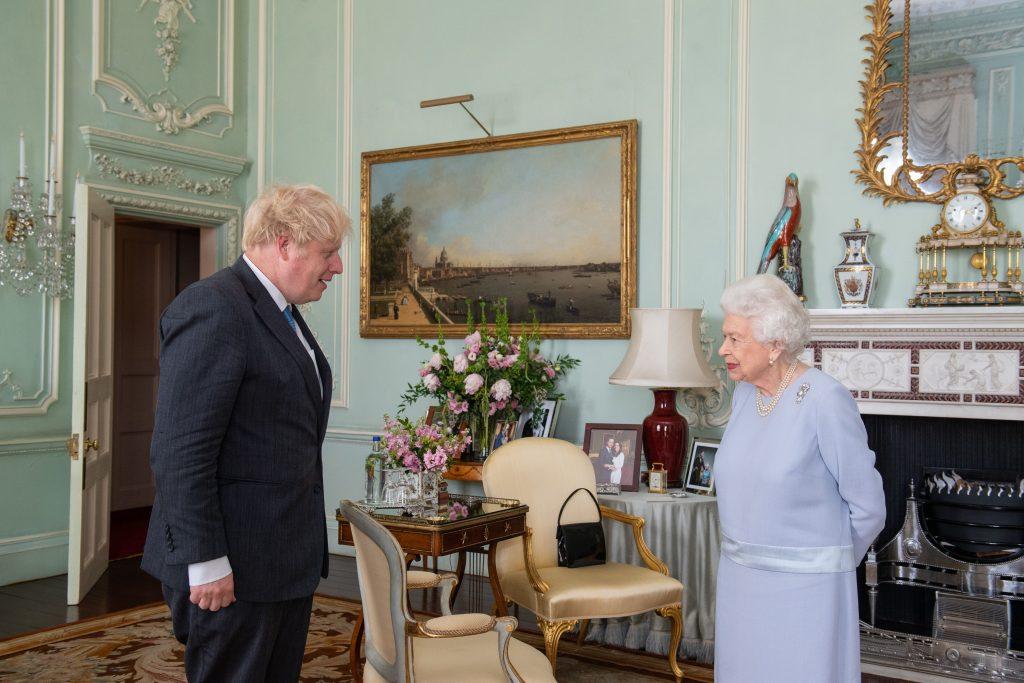 La reine Elizabeth II salue le Premier ministre Boris Johnson lors de la première audience hebdomadaire en personne avec le Premier ministre depuis le début de la pandémie de coronavirus, au palais de Buckingham, le 23 juin 2021.