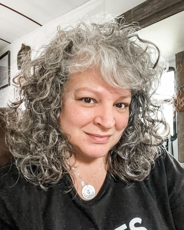 Coupe mi-longue pour les femmes de la cinquantaine aux cheveux bouclés.