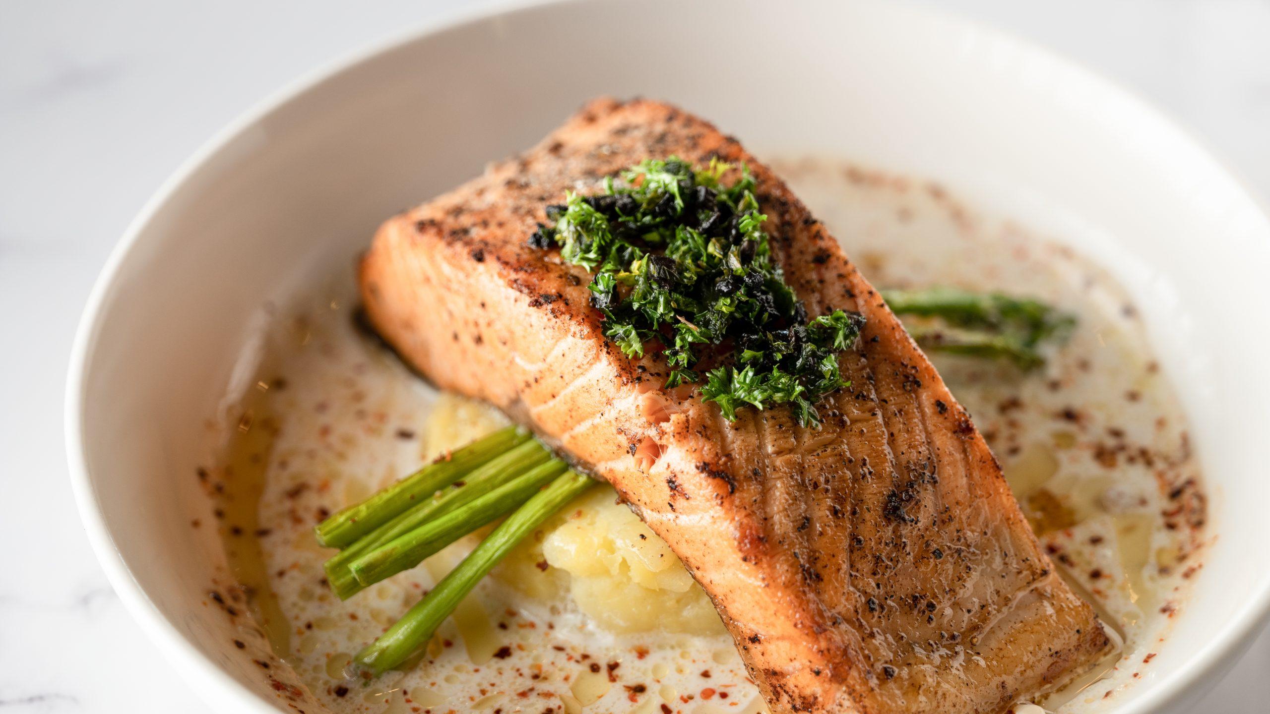 Un filet de saumon dans un bol avec des haricots verts et de la pomme de terre écrasée.