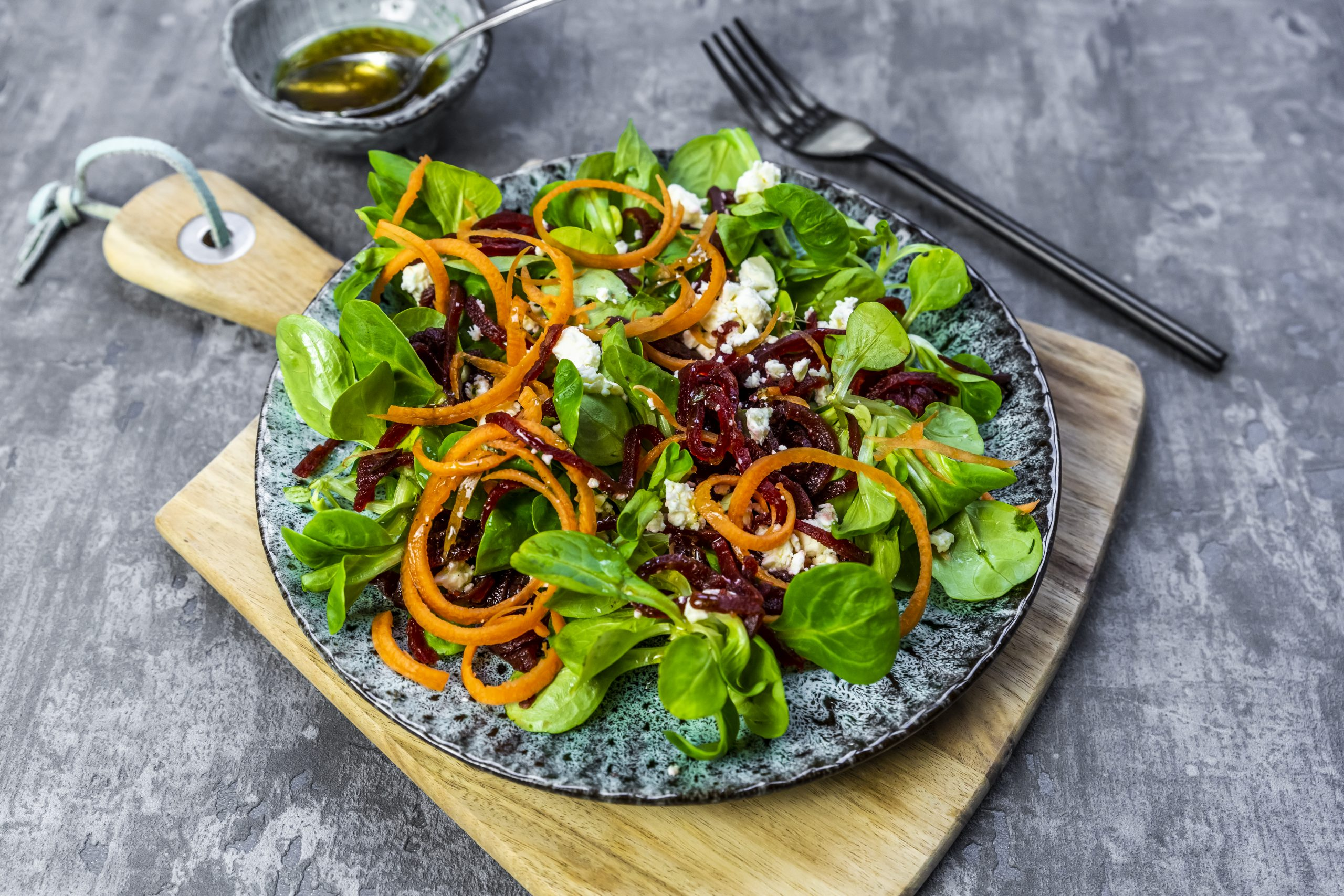 Une salade verte sur une assiette et une planche à découper.