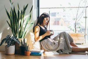 Jeune femme buvant du café à côté d'une plante d'intérieur, lisant des livres.
