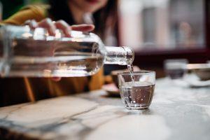 Femme versant de l'eau dans un verre à partir d'une bouteille à une table.