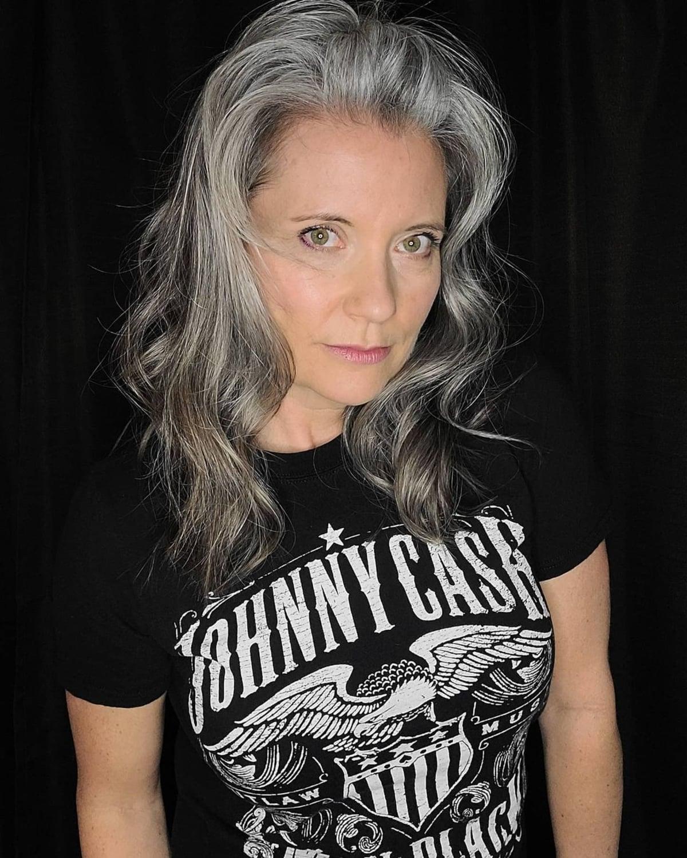 Cheveux mi-longs ondulés pour les femmes de plus de 60 ans avec des cheveux gris.