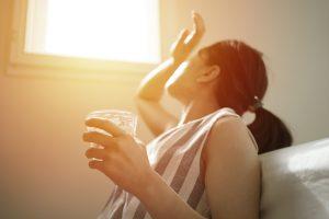 Femme buvant de l'eau et regardant le soleil.
