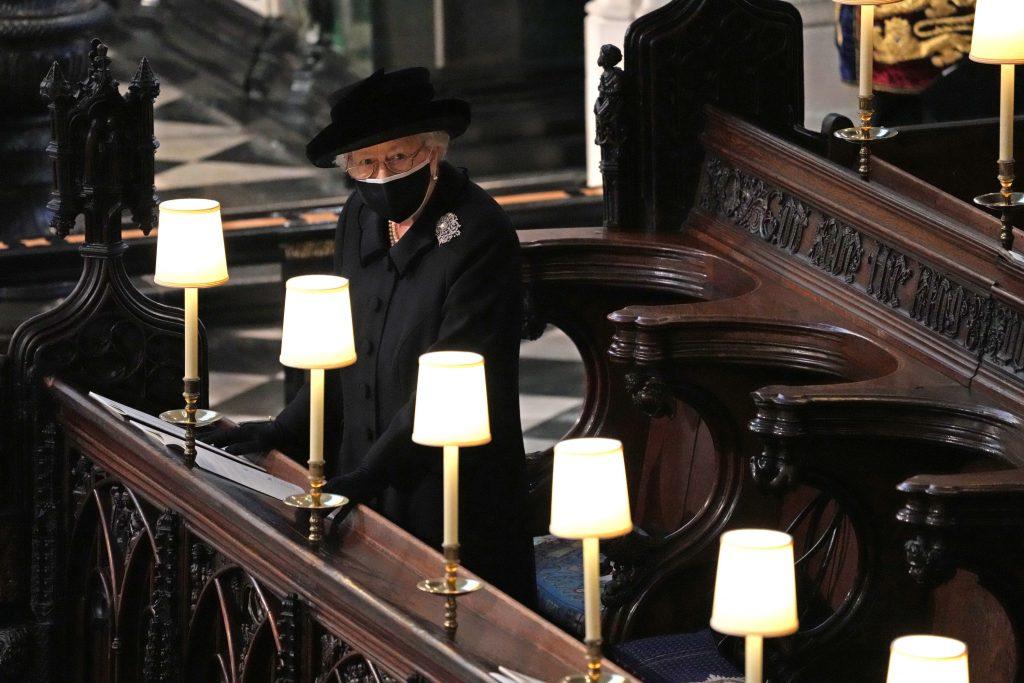 La reine Elizabeth II regarde les porteurs de cercueils transporter le cercueil du prince Philip, duc d'Édimbourg dans la chapelle Saint-Georges lors des funérailles du prince Philip, duc d'Édimbourg au château de Windsor, le 17 avril 2021 à Windsor, au Royaume-Uni.
