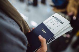 Une femme tient ses passeports avant de prendre l'avion avec le statut de vaccin approuvé Covid-19