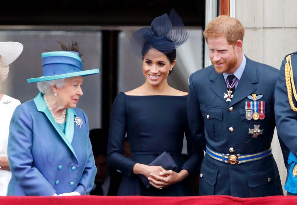 La reine Elizabeth II, Meghan, duchesse de Sussex, et le prince Harry, duc de Sussex, regardent un défilé aérien pour marquer le centenaire de la Royal Air Force depuis le balcon du palais de Buckingham, le 10 juillet 2018 à Londres, en Angleterre.