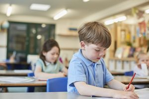 Jeune garçon assis dans une salle de classe