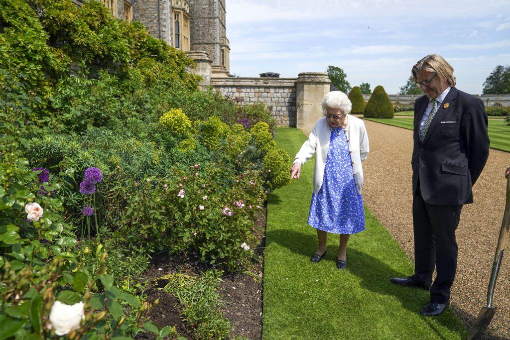 La Reine Elizabeth II regarde un parterre de fleurs avec le Président de la Royal Horticultural Society, Keith Weed, après qu'il lui ait présenté une rose du Duc d'Edimbourg, nommée en mémoire de son défunt mari le Prince Philip, le Duc d'Edimbourg, au Château de Windsor à Windsor, à l'ouest de Londres, le 2 juin 2021.