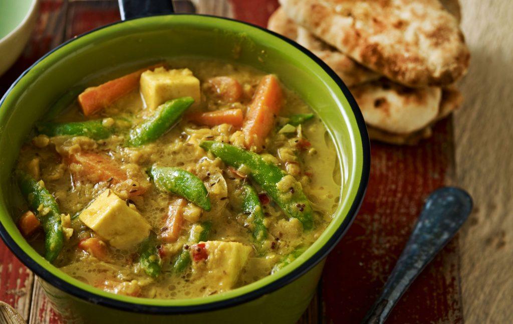 Curry de pois cassés dans un bol en émail vert avec une cuillère et du pain à l'extérieur.