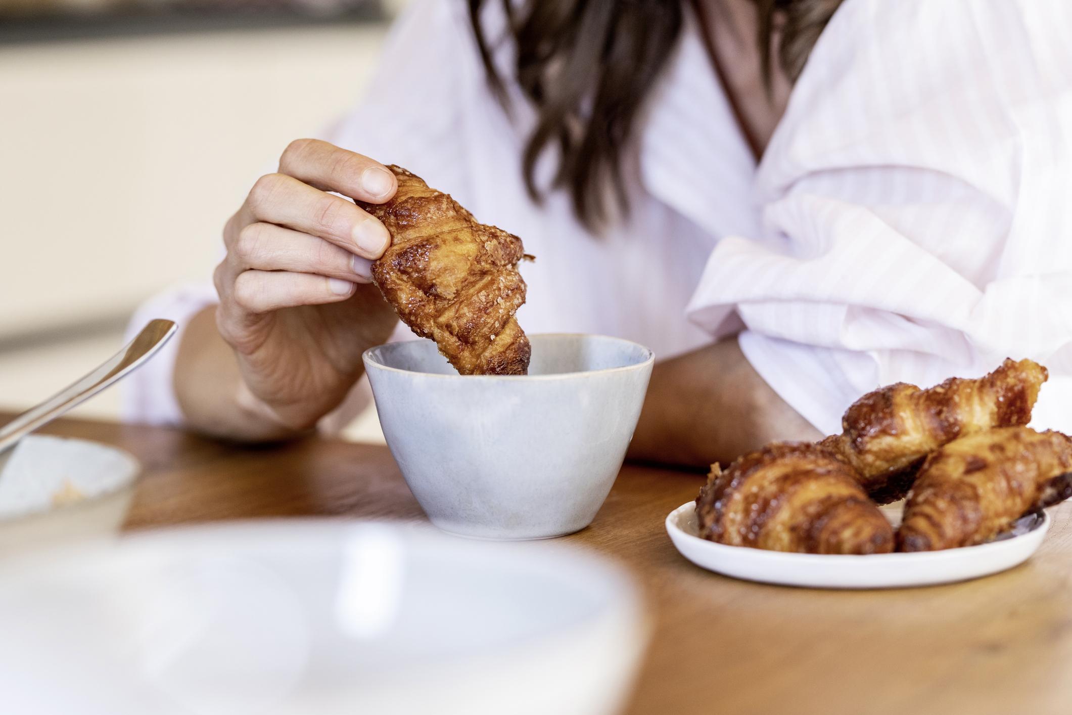 Femme trempant le croissant du petit-déjeuner dans le café