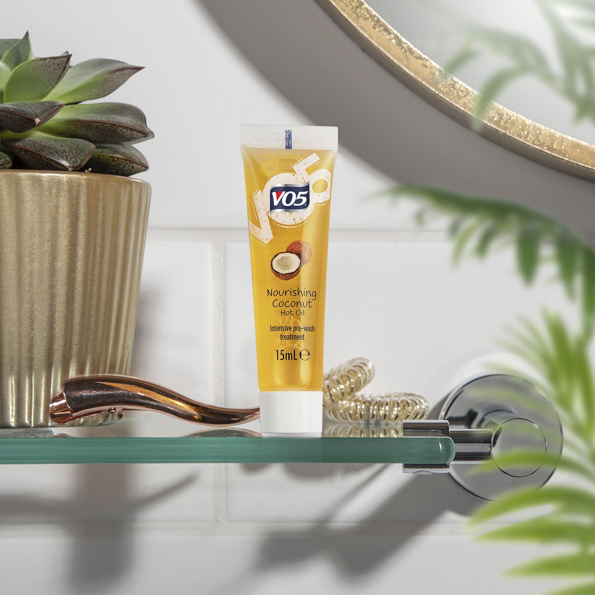 Les traitements à l'huile chaude : Prise de vue de l'huile de noix de coco nourrissante VO5 dans une salle de bain, avec des plantes contre un mur blanc.