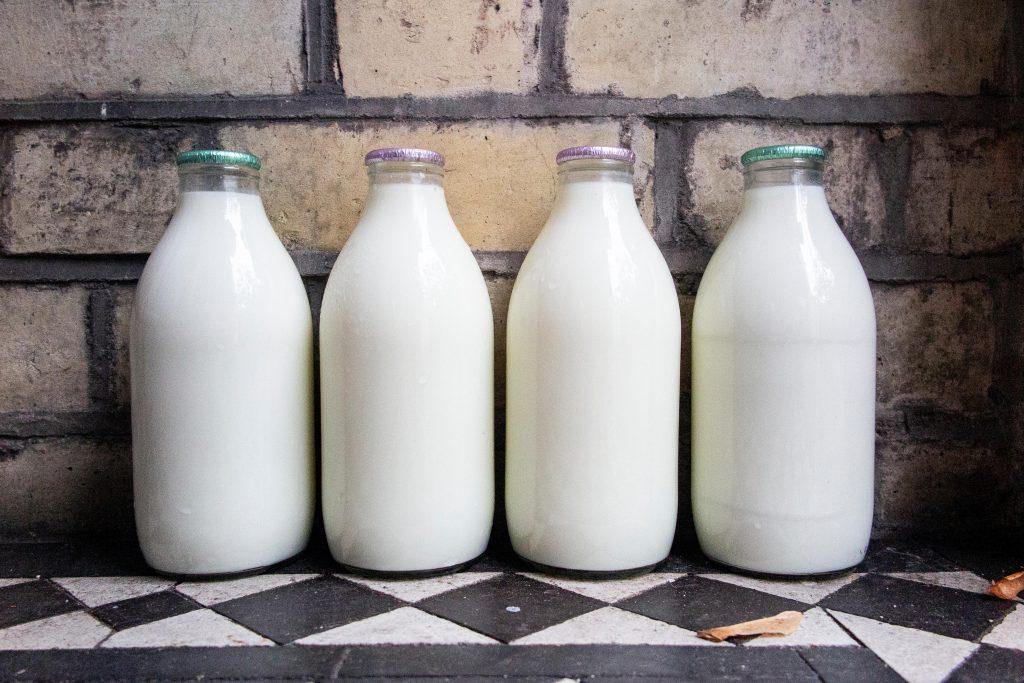 Quatre bouteilles de lait sur le pas de la porte d'une maison mitoyenne à Londres.