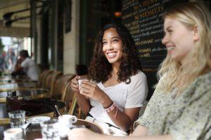 Une femme boit un café à l'extérieur d'un café alors que la feuille de route du verrouillage se développe.