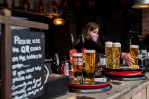 Une femme sert des boissons à l'extérieur alors que le plan de confinement se poursuit en Angleterre.