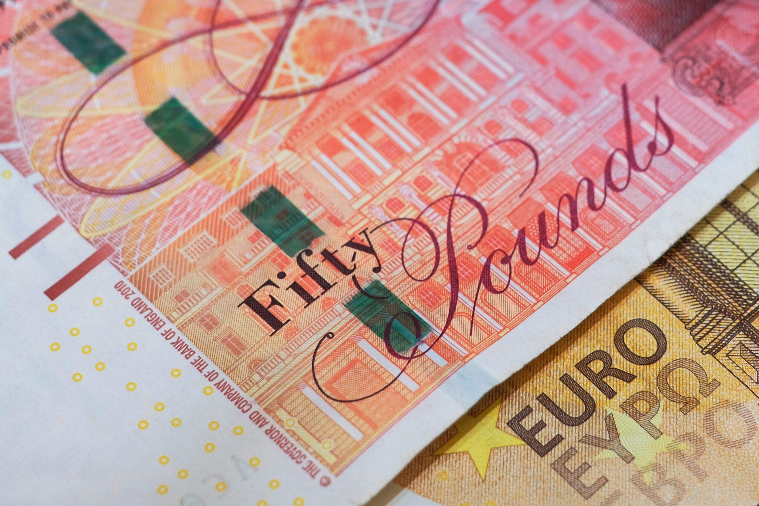 Un billet de 50 livres sterling est posé sur un billet de 50 euros.