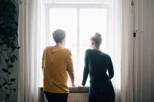 Couple regardant par une fenêtre dans la maison